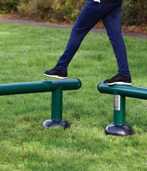 image of child playing on steel balance beams