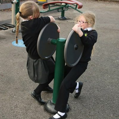 image of two primary school children playing on outdoor fitness equipment