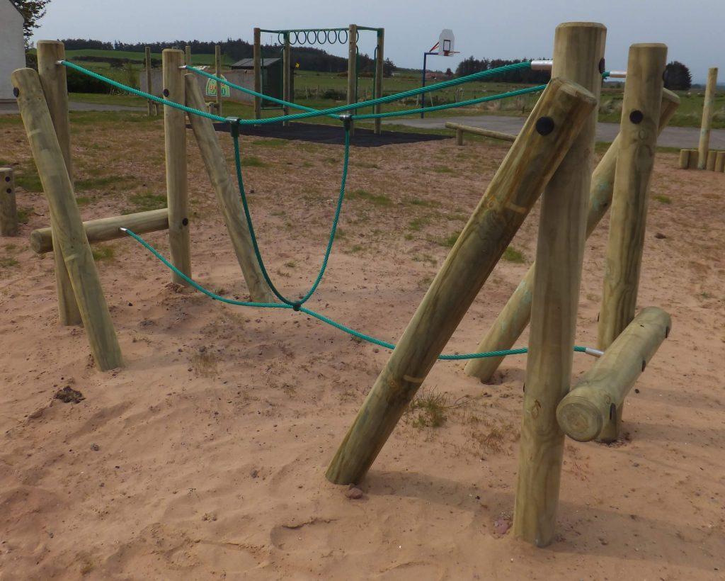 wooden trim trail item Burma Bridge installed onto play sand