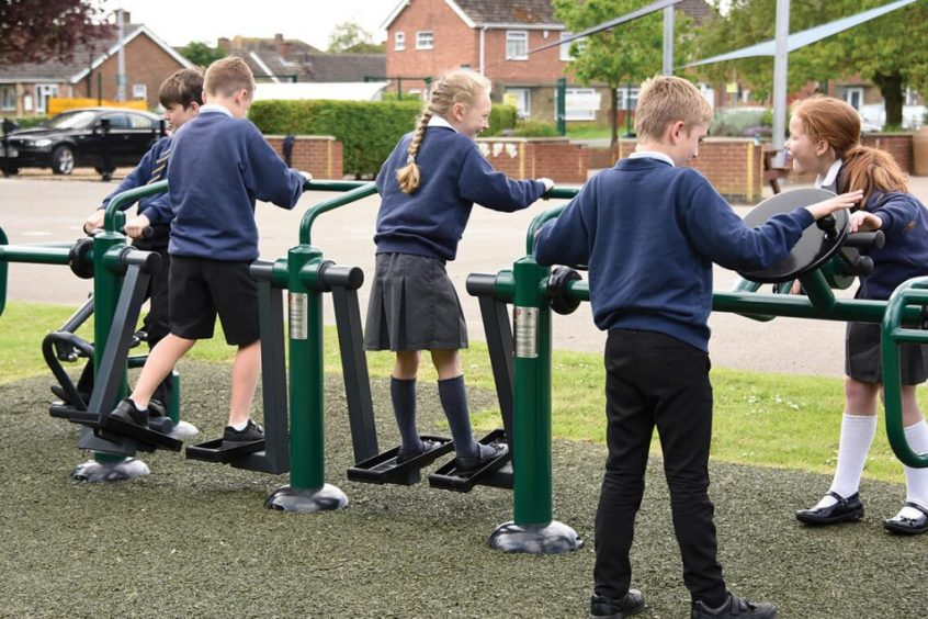 image of children using a combination outdoor gym unit in a school