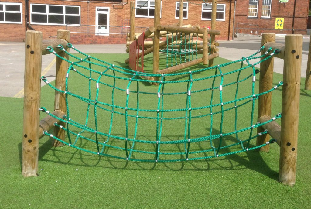 wooden trim trail item rope tunnel installed onto artificial grass surfacing