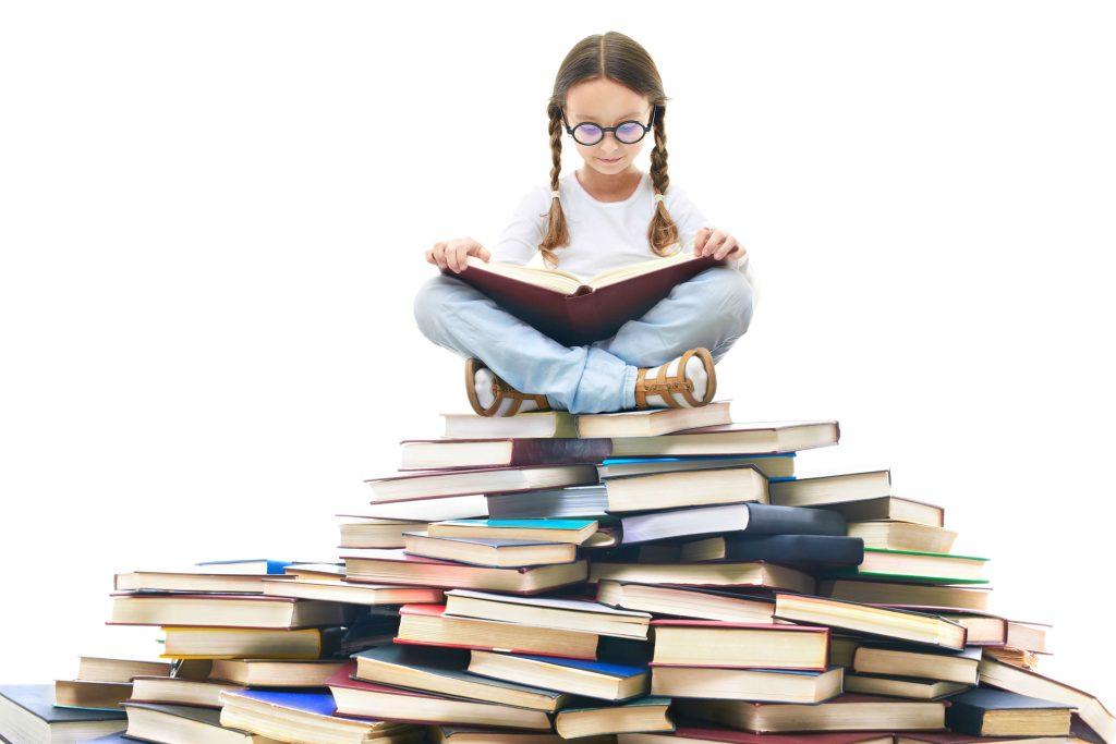 image of a school girl reading a book on a pile of books