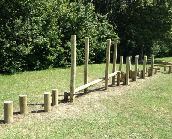 stepping logs and wooden balance beam which creates a balancing trail in a school